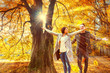 canvas print picture - Couple Throwing up Leaves in Autumn