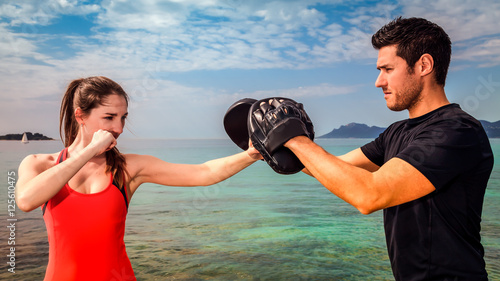 Fotobehang Vechtsport Young woman boxing training with sparring partner: girl doing punch