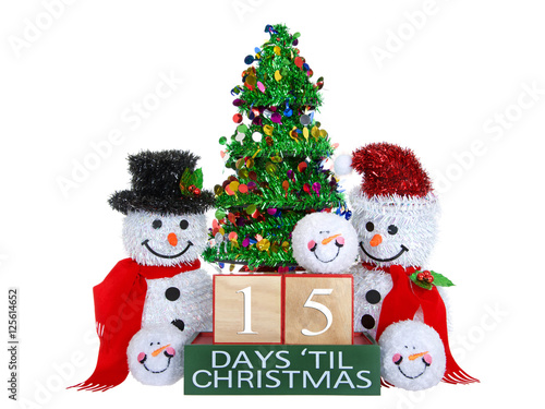 Fotografie, Obraz  15 Days until Christmas light beech wood blocks with red trim on a green base with tinsel christmas tree, mr and mrs snowman and snowball snowmen heads isolated on a white background