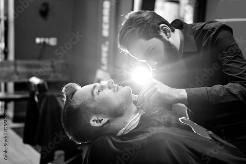 The Barber man in the process of cutting the beard of a client in a Barbershop, Canvas Print