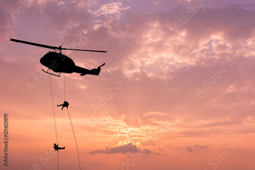 Tuinposter Helicopter Silhouette of helicopter, soldiers rescue helicopter operations on sunset sky background.