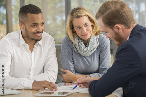 Valokuva  Mutiracial couple with a .real estate agent