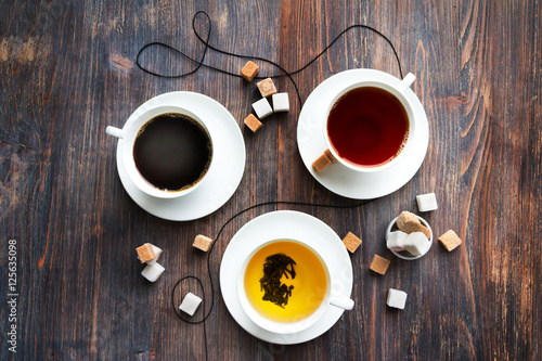 Fotografía  Tea, black tea, green tea, black espresso coffee in white porcelain cups on rustic wooden table
