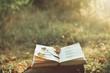 Leinwanddruck Bild - Vintage book of poetry outdoors