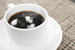 aroma hot black coffee with bokeh and smoke in white cup on the