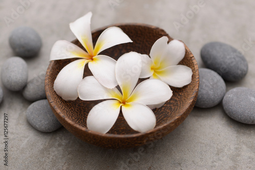 Foto auf Gartenposter Spa Beautiful Composition of frangipani in wooden bowl with spa stones