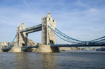 Fototapeta na wymiar Scenic landscape view of Tower Bridge standing tall in afternoon light above the River Thames as viewd from the South Bank in London, England