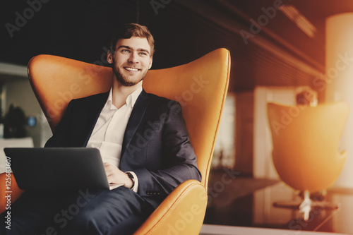 Young smiling successful man entrepreneur in formal business suite with a beard sitting on orange armchair with laptop in luxury office interior