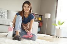 Young Woman Cleaning Carpet In Room