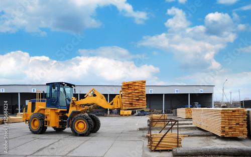 Zdjęcie XXL Pomarańczowy wózek widłowy transportuje deski w zakładzie do obróbki drewna.