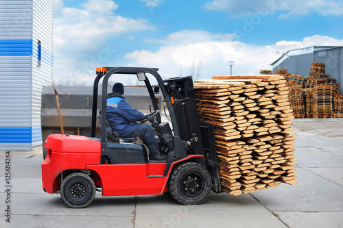 Zdjęcie XXL Czerwony wózek widłowy transportuje deski w zakładzie do obróbki drewna.