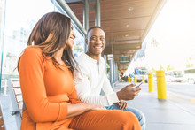 Black Couple Waiting For The Bus At Station