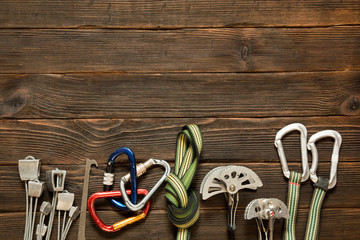 rock climbing and travel equipment on dark wooden background, to