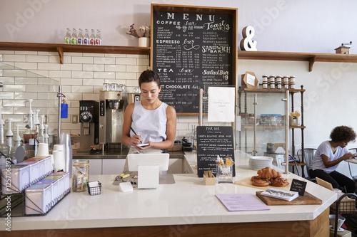 Láminas  Waitress writing customer's order at counter of coffee shop