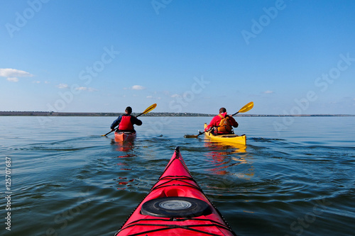 Two guys in a kayak. Kayaking in the calm blue lake. View from the red kayak.