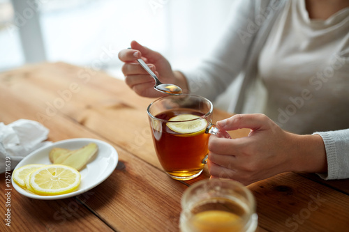 Photo  close up of woman adding honey to tea with lemon