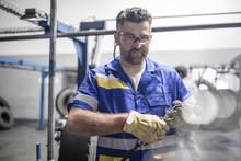 Repairman Holding Tire Tread Cutting Machine