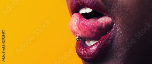 Fototapeta African girl tongue stuck out showing piercing letterbox
