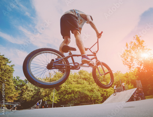 Boy jumping with his bmx in the park. Wallpaper Mural