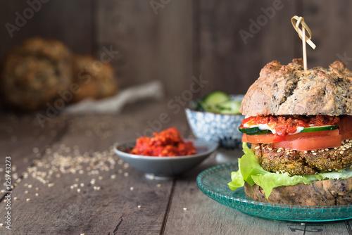 hamburger vegetariano con pane fatto in casa; verdure e salse in ciotole di ceramica. Sfondo rustico di legno