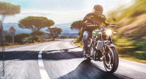 Foto  Motorrad fährt auf freier Landstrasse in den Sonnenuntergang
