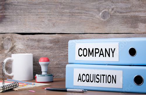 Photo Company and Acquisition. Two binders on desk in the office. Busi