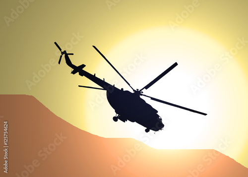 Photo  illustration of silhouette of military helicopter MI-17 flying over the desert i