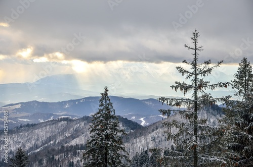 Winter mountain landscape. High mountain peaks through the clouds. - 125754885