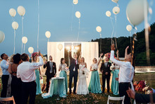 Newlyweds And Their Friends Pull Balloons In The Air After The C
