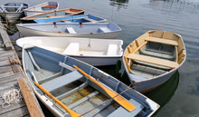 Small Boats At A Dock:  Several Rowboats Tied To A Wooden Pier Sit Quietly On Bay In Maine.