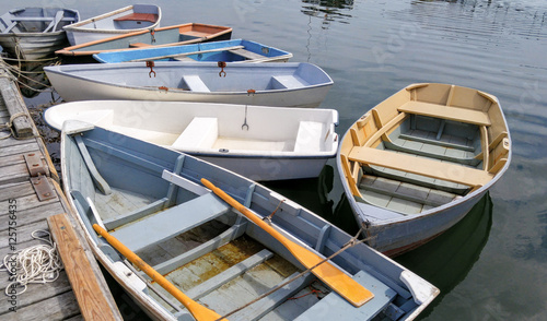 Small Boats at a Dock:  Several rowboats tied to a wooden pier sit quietly on bay in Maine Wallpaper Mural