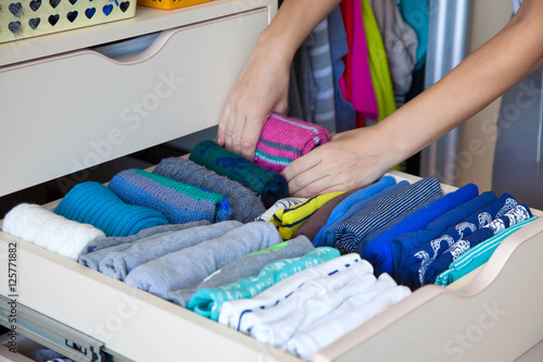 Fotografía  The woman folds knitted leg warmers in a drawer. A woman is tidy