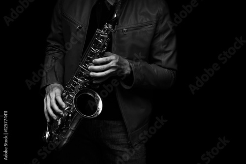 Photo  Jazz saxophone musician in the leather jacket, closeup.