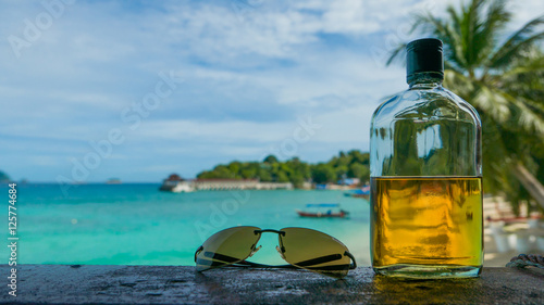 Photo Beach party. Holiday fun concept. Bottle of rum and sunglasses w