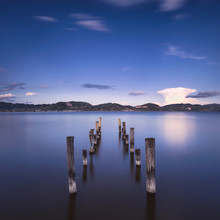 Wooden Pier Or Jetty Remains On A Blue Lake On Sunset. Italy