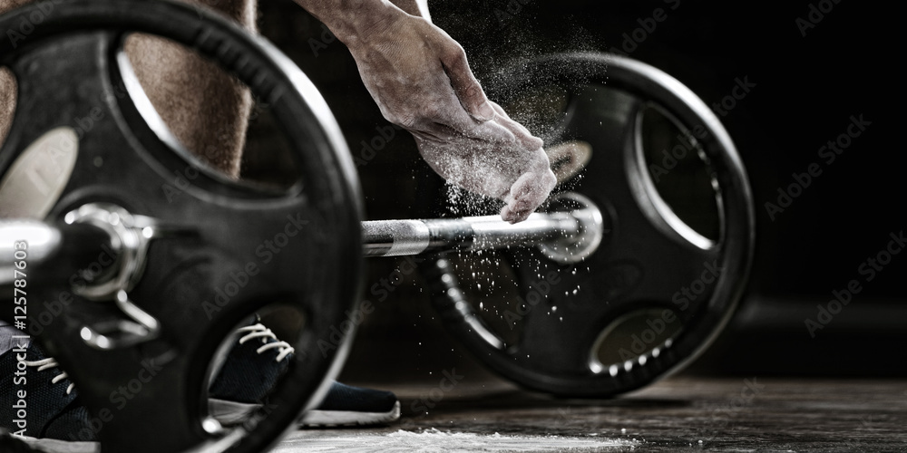 Fototapety, obrazy: Sports background. Young athlete getting ready for weight lifting training. Powerlifter hand in talc preparing to bench press