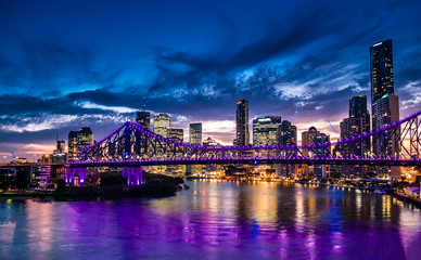 Fototapeta na wymiar Vibrant night time panorama of Brisbane city with purple lights