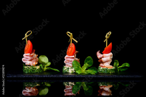 Fotomural canapes bacon tomato on black background with reflection