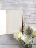 Open notebook or diary, journal with white flowers on grey and white wooden table