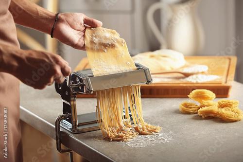 Man using pasta machine to prepare spaghetti, close up view Fototapeta