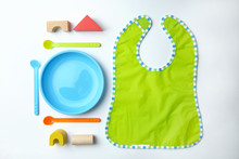 Bright Baby Tableware And Bib On White Background