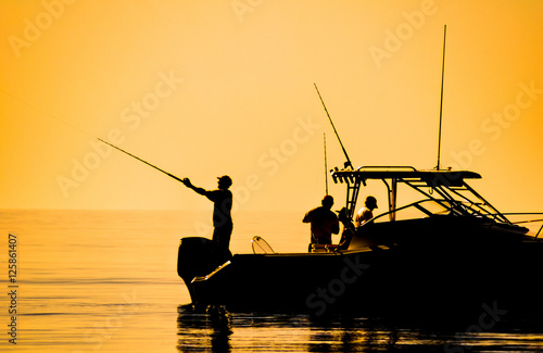 Poster de jardin Peche silhouette of sport fishing boat reflecting on calm water