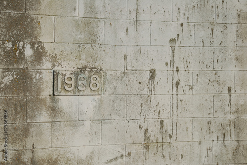 Fotografia  Building's birthdate (1968) on dirty cinderblock wall