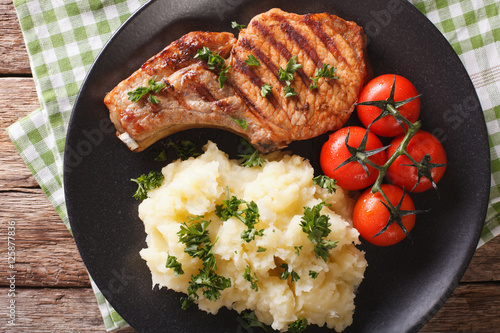 In de dag Grill / Barbecue Grilled pork T-bone steak garnished with mashed potatoes close-up. Horizontal top view