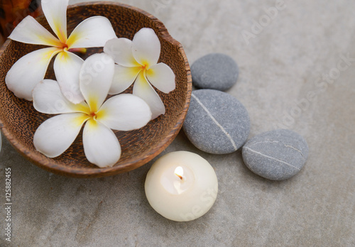 Staande foto Spa frangipani in wooden bowl with spa stones ,candle on grey background.