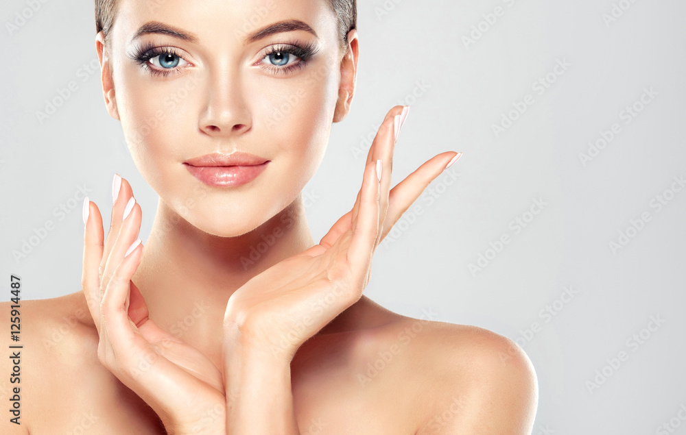 Fototapeta Beautiful Young Woman with Clean Fresh Skin  touch own face . Facial  treatment   . Cosmetology , beauty  and spa .