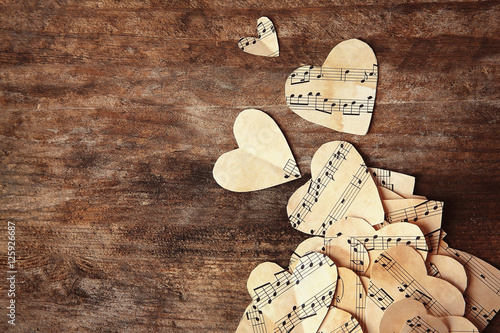 Paper hearts with music notes on wooden background
