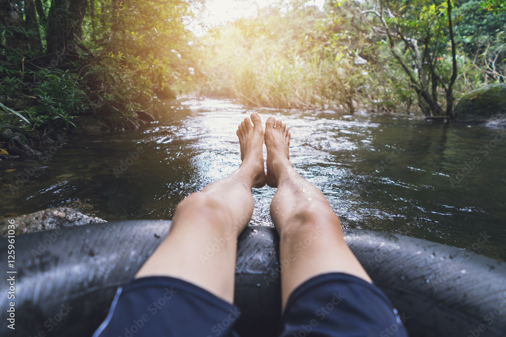 Fototapety, obrazy: Man floating down a canal in a blow up tube