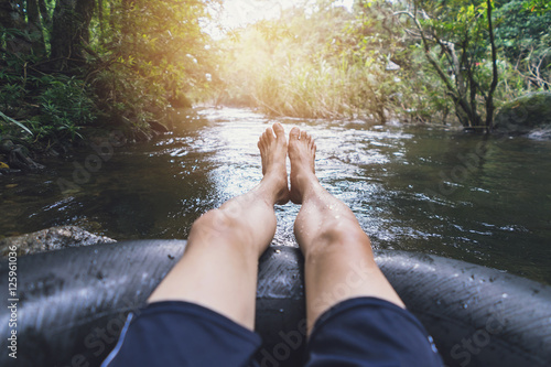 Man floating down a canal in a blow up tube