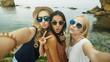 Three beautiful ladies taking selfies.